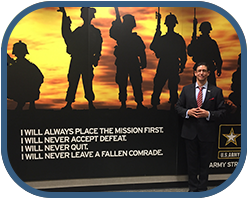 Rafael A. Ortiz in a suit in front of soldier backdrop