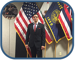 Rafael A. Ortiz in a suit in front of flags